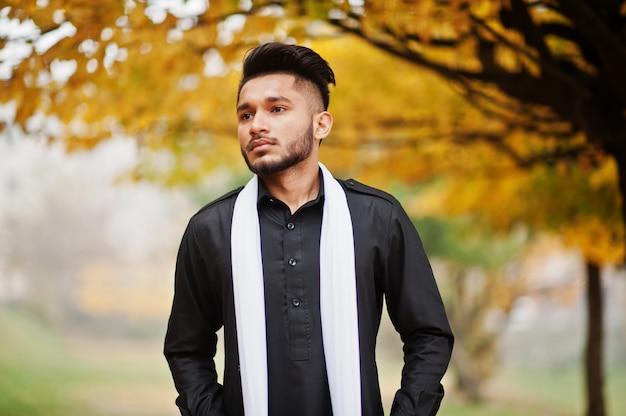 L'uomo alla moda indiano in vestiti tradizionali neri con la sciarpa bianca ha posato all'aperto contro l'albero giallo delle foglie di autunno.