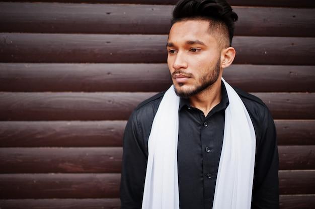 L'uomo alla moda indiano in vestiti tradizionali neri con la sciarpa bianca ha posato all'aperto contro la parete di legno