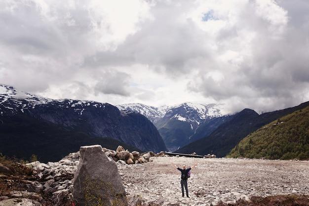 L'uomo alza le mani in posa davanti a splendide montagne in norvegia