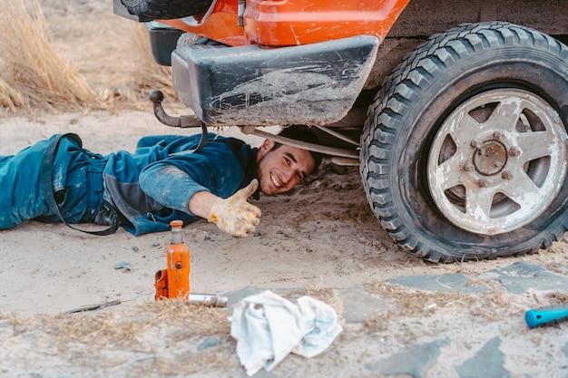 L'uomo alza su un jack 4x4 fuori dal camion della strada