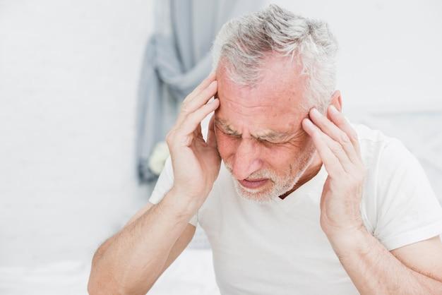 L'uomo anziano con un mal di testa