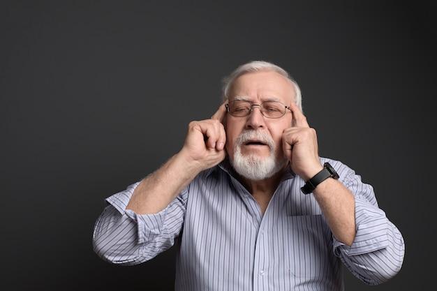 L'uomo anziano dai capelli grigi mostra un dito verso l'alto con un sorriso