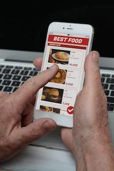 L'uomo anziano di affari con il telefono che ordina porta via il cibo