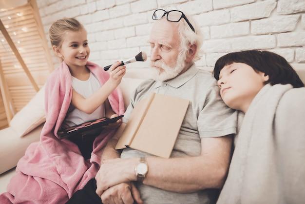 L'uomo anziano dorme con il libro i nipotini si divertono.