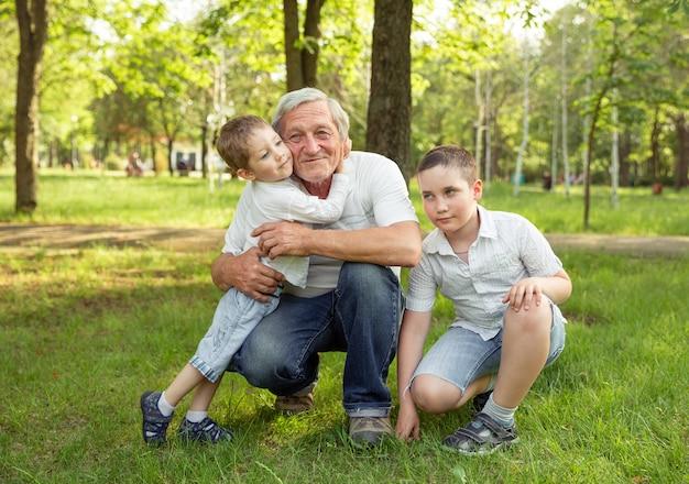 L'uomo anziano ed i nipoti stanno abbracciando e sorridendo, riposando insieme