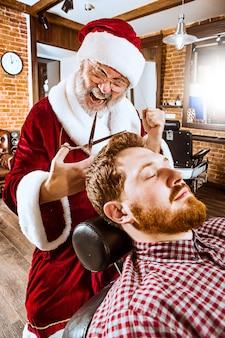 L'uomo anziano in costume di babbo natale lavora come maestro personale con le forbici al negozio di barbiere prima di natale