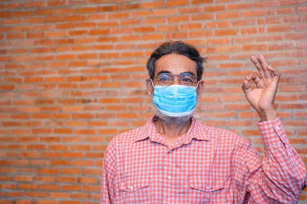 L'uomo anziano indossa una maschera protettiva contro le malattie infettive e l'influenza