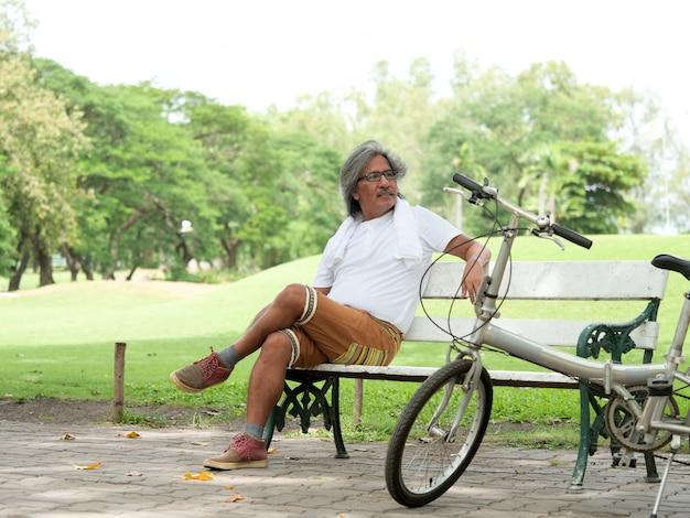 L'uomo anziano si riposa nel parco dopo il ciclismo