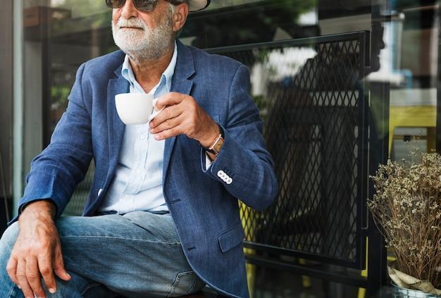 L'uomo anziano si sta godendo un caffè
