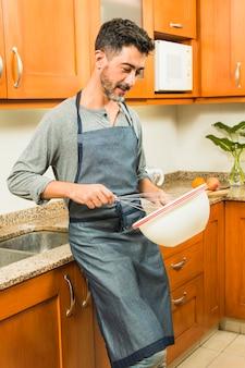 L'uomo appoggiato al bancone della cucina ha battuto l'uovo con la frusta nella ciotola