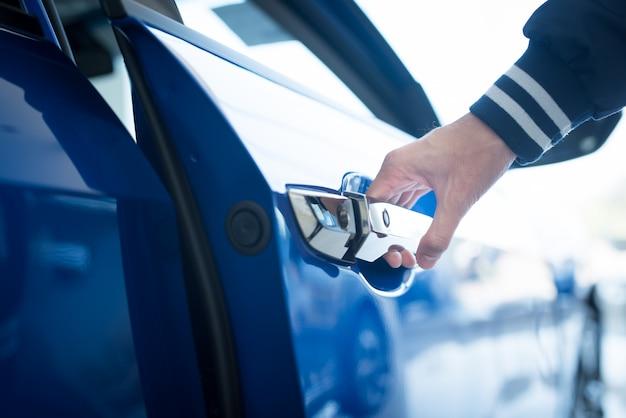L'uomo apre le porte a una nuova auto, ispezione auto nello showroom