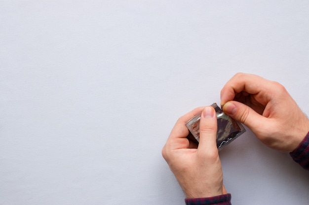 L'uomo apre un preservativo su uno sfondo bianco con spazio per il testo