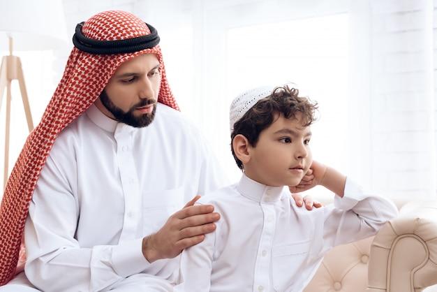 L'uomo arabo chiede perdono al figlio piccolo offeso.