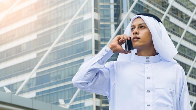 L'uomo arabo si leva in piedi e usa il telefono cellulare allo spazio urbano all'aperto al giorno di mattina
