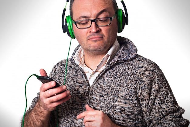 L'uomo ascolta musica e guardando il cellulare con sguardo perplesso