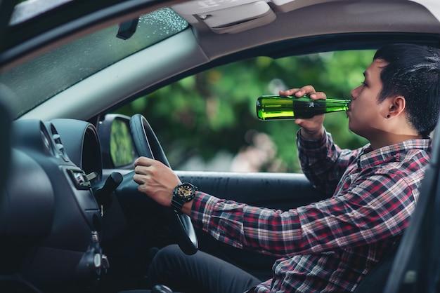 L'uomo asiatico beve una bottiglia di birra mentre sta guidando una macchina