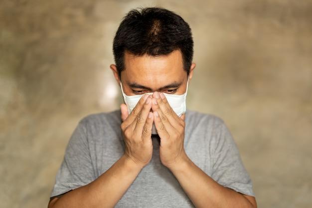 L'uomo asiatico che indossa una maschera con la mano copre la bocca mentre tossisce.