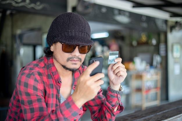 L'uomo asiatico dei pantaloni a vita bassa sta tenendo le carte di credito e sta utilizzando i telefoni cellulari per lo shopping online.