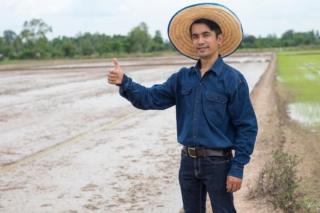 L'uomo asiatico del coltivatore indossa la camicia e il cappello blu con il pollice sulla mano dell'azienda agricola del riso verde.