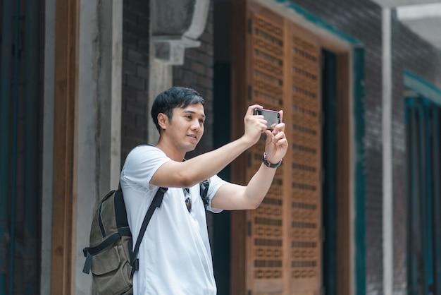 L'uomo asiatico del viaggiatore che per mezzo del telefono cellulare prende un'immagine mentre passa il viaggio di festa a pechino, cina