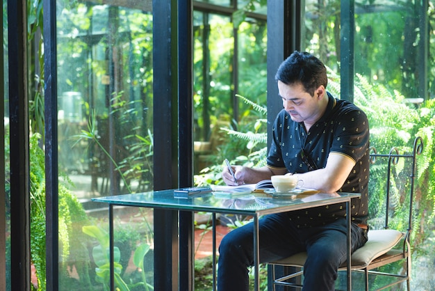 L'uomo asiatico di affari pakistani in casuale che indossa casuale scrive sul taccuino facendo uso del telefono cellulare con la tazza di caffè in caffè, concetto indipendente di affari.