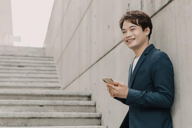 L'uomo asiatico di affari sta sorridendo e sta tenendo sul suo telefono cellulare