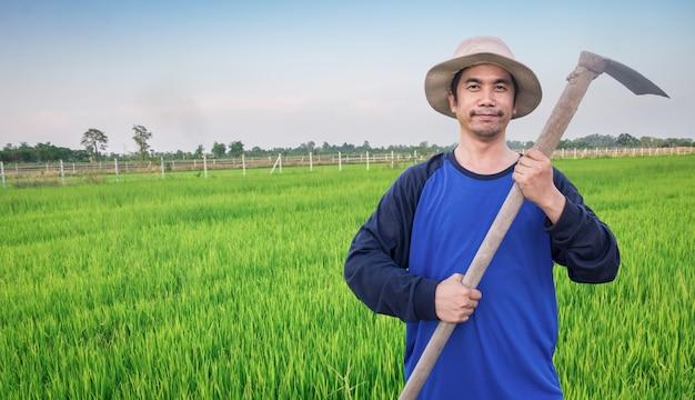 L'uomo asiatico felice del ritratto sta sorridendo, agricoltore che sta in una camicia blu