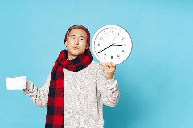 L'uomo asiatico in inverno caldo copre la posa con l'orologio
