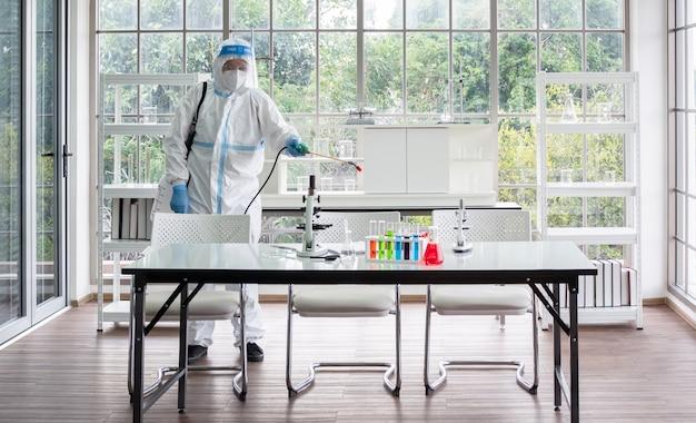 L'uomo asiatico indossa tute protettive personali o dpi, occhiali e maschera per il viso, facendo disinfezione e decontaminazione nella stanza del laboratorio di scienza e microbiologia.