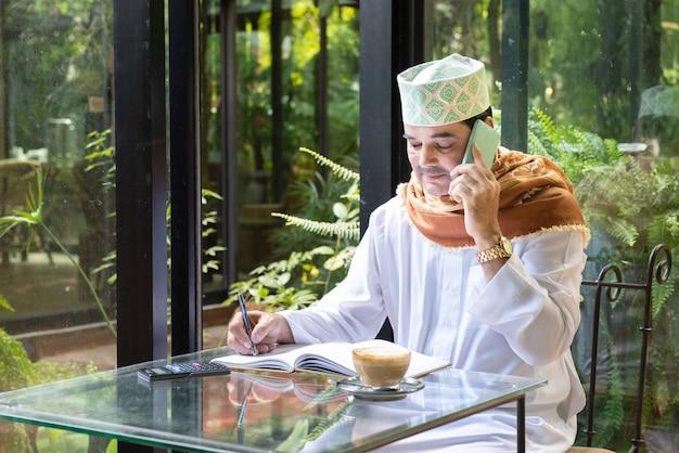 L'uomo asiatico pakistano di affari in casuale che indossa casuale scrive sul taccuino facendo uso del telefono cellulare astuto con la tazza di caffè in caffè