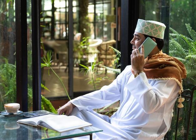 L'uomo asiatico pakistano di affari in casuale che indossa casuale scrive sul taccuino facendo uso del telefono cellulare astuto