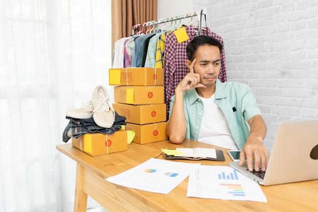 L'uomo asiatico pensa al computer portatile funzionante serio duro a casa che vende online