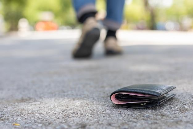 L'uomo asiatico perde il portafoglio nero sulla strada nell'attrazione turistica