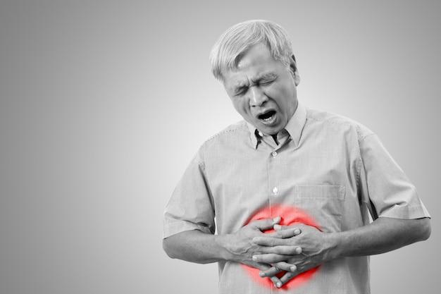 L'uomo asiatico più anziano sta avendo il concetto di dolore di dolore di stomaco con fondo isolato.