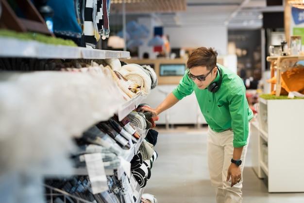 L'uomo asiatico si è vestito nello stile casuale e porta i vetri dell'occhio e il trasduttore auricolare che sceglie i pantaloni e fa