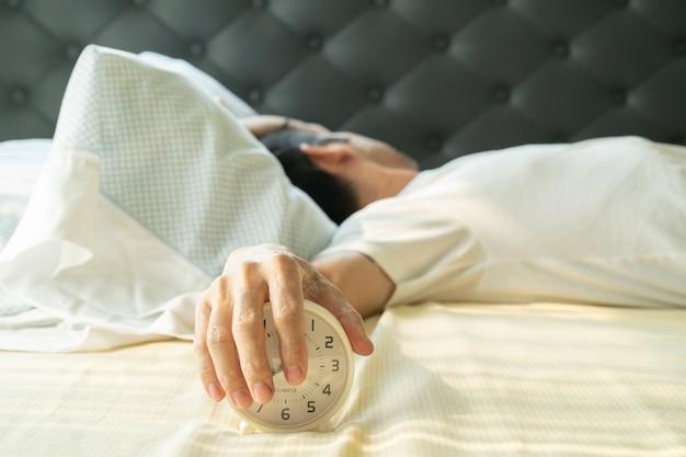L'uomo asiatico si sveglia di mattina e la mano che raggiunge la sveglia