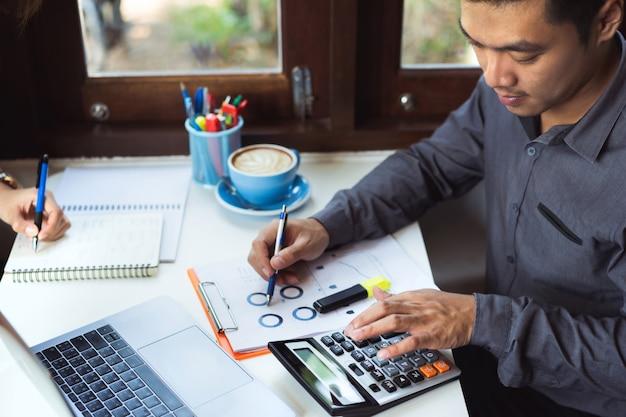 L'uomo asiatico sta calcolando i dati aziendali