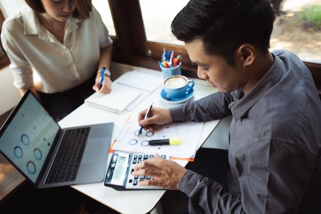 L'uomo asiatico sta calcolando le spese di affari con il compagno
