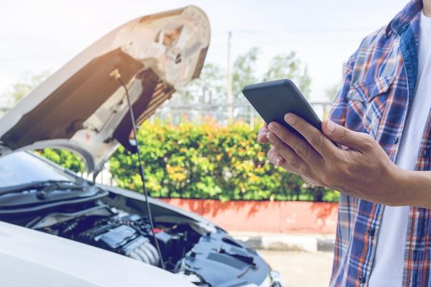 L'uomo asiatico sta davanti a una macchina rotta chiedendo assistenza
