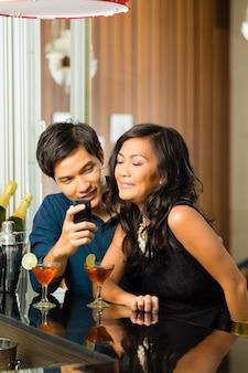 L'uomo asiatico sta flirtando con la donna nella barra