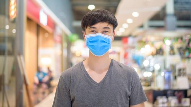 L'uomo asiatico sta indossando la maschera chirurgica nel centro commerciale