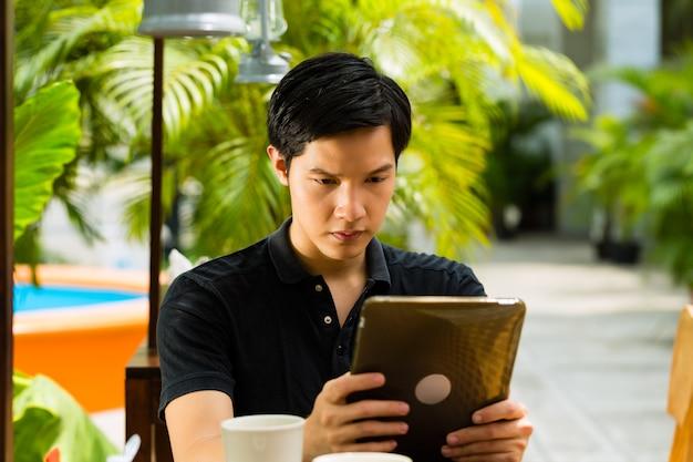 L'uomo asiatico sta sedendosi in un bar o in un caffè all'aperto