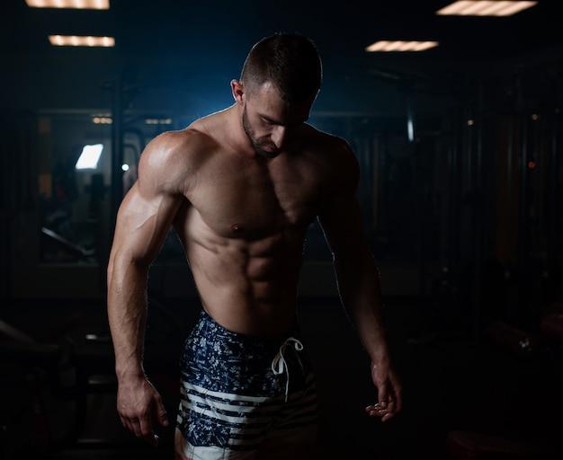 L'uomo atletico con un corpo muscoloso si pone in palestra, mostrando i suoi muscoli