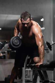 L'uomo atletico si allena con le teste di legno, pompando il suo bicipite
