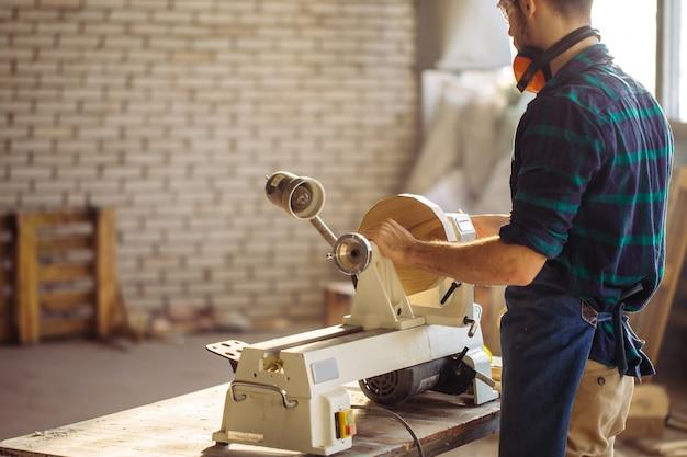 L'uomo attraente inizia a fare la falegnameria in carpenteria