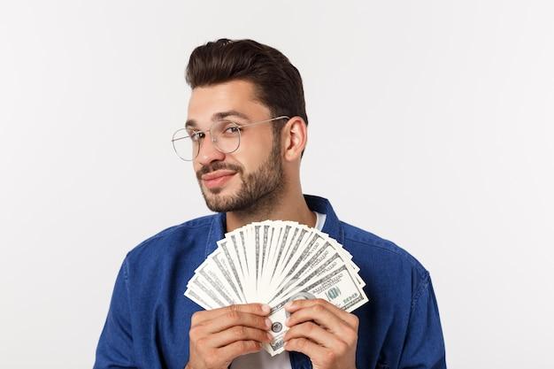 L'uomo attraente sta tenendo il denaro contante in una mano, sopra