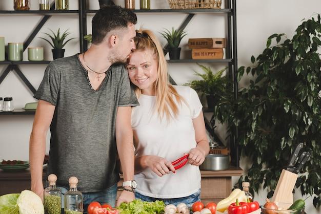 L'uomo bacia la sua ragazza sulla fronte tenendo i peperoncini rossi in cucina
