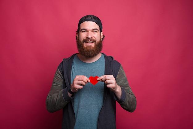 L'uomo barbuto allegro che indossa un cappuccio sta tenendo un piccolo cuore rosso
