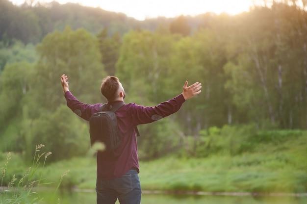 L'uomo barbuto alzò le mani verso il sole al tramonto. ottima vista sulla valle