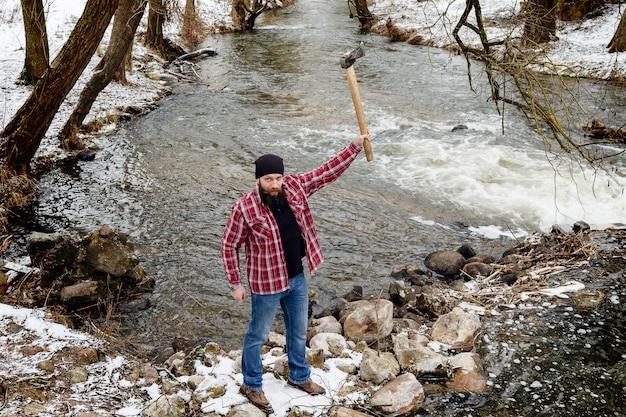 L'uomo barbuto arrabbiato con un'ascia passa attraverso la foresta dell'inverno
